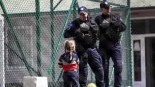 Image shows a young Kosovar child looking at Kosovar police officers