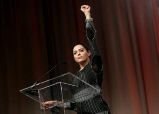 La actriz estadounidense Rose McGowan levanta su puño frente a un atril.