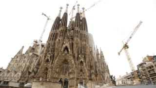 Tourists stand outside the Sagrada Familia in Barcelona