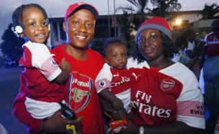 A family, fans of Arsenal, pose for a photo during the arrival of Former soccer coach Arsene Wenger at the Roberts International Airport in Harbel, Liberia, 22 August 2018.
