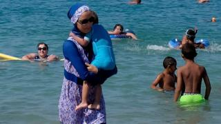 A woman wearing a burkini walks in the water on a beach in Marseille, France on 27 August