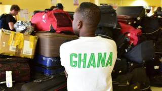 A man wearing a tee shirt on which is written 'Ghana' on the back, stands next to the pile of suitcases belonging to Ghana's national football team players and officials, at the airport