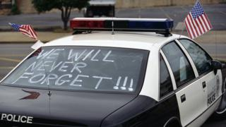 "One month after the Oklahoma City bombing, a police car carries American flags and the words, ""We Will Never Forget!!!"""