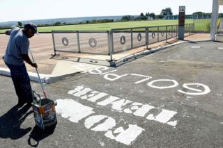 "A worker removes the inscription ""Temer Out"" written on the street in front of the entrance of the Alvorada Palace presidential residence on 1 September 2016 in Brasilia"