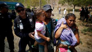 A family of Central American migrants is detained by Federal Police during a raid on their journey towards the United States