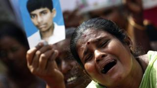 File picture of a Tamil woman crying as she holds up an image of her missing family member at a 2013 protest in Jaffna