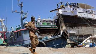 جندي صومالي يحمل السلاح في ميناء بوصاصو الصومالي