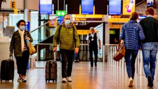 Travellers wearing face masks as a precaution, at KLM side at the Schiphol airport during the covid - 19 pandemic.
