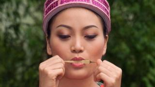 Una joven usando un arpa para silbar