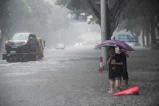 People holding umbrellas wade through floodwaters amid heavy rainfall on a street after super typhoon Lekima made landfall in Ningbo