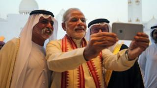 Indian Prime Minister Narendra Modi, middle, takes a selfie next to Sheikh Hamdan bin Mubarak Al Nahyan, UAE Minister of Higher Education and Scientific Research, left, as they tour the Sheikh Zayed Grand Mosque during the first day of his two-day visit to the UAE, in Abu Dhabi, United Arab Emirates, Sunday, Aug. 16, 2015.
