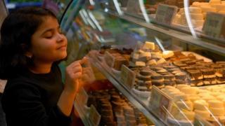 طفلة تنظر إلى أنواع الشوكولاتة في متجر لبيع الحلويات