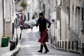 мужчина в шотландской юбке на улицах Монмартра в Париже