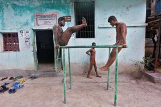 Wrestlers exercise at a traditional Indian wrestling training centre