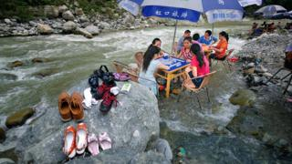 Mahjong players in a river