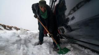 Said, 43, removes snow with a shovel around his vehicle stuck in the snowy and twisty roads, 60km from Azilal city, central Morocco, 05 March 2018 (issued 07 March 2018). Azilal is a city in central Morocco, in the Atlas Mountains,
