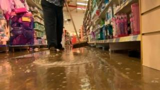 Woman sweeping flood water out from her shop