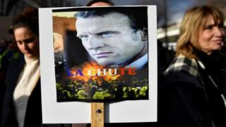 "A woman holds a placard bearing a photo of French President Emmanuel Macron with the words ""La Chute"" (The Fall) during a protest against the pension overhauls, in Marseille, southern France, on 5 December, 2019."