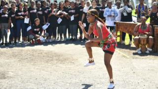 A dancer entertains the crowds at the township in Cape Town ahead of the royal visit South Africa
