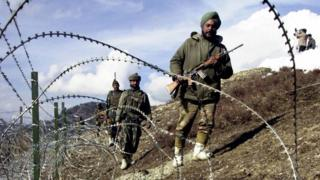 Armed Indian soldiers patrolling along a barbed-wire fence, on the Line of Control between Pakistan and India, 2003