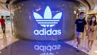 Shoppers wearing face masks walk past the Adidas logo in a mall.