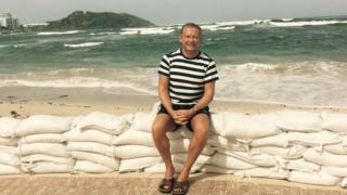 Alex Woolfall sitting on sandbags