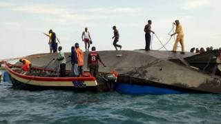 Volunteers work at the scene of a capsizing in Tanzania