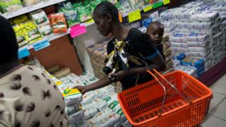 A woman buys a packet of maize flour subsidised by the government at a supermarket in Kenya's capital, Nairobi, on Wednesday.