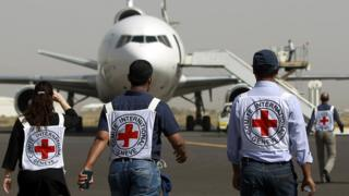 International Committee of the Red Cross (ICRC) staff walk towards an aid plane on the runway at Sanaa's international airport (11 April 2015)