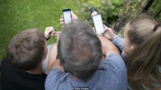 Tres personas con sus móviles.