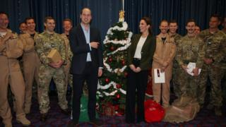 The Duke and Duchess of Cambridge standing by a Christmas tree at RAF Akrotiri base