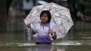 Woman wading through flooded street