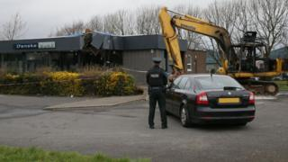 A police officer and the digger at the Danske Bank branch in Newtownabbey