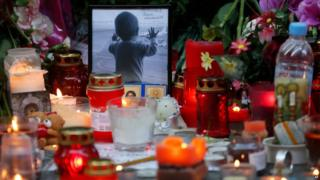 Portrait of 10-month-old Darina Gromova next to flowers and candles at Pulkovo airport near St Petersburg, 2 November 2015