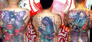 Three Japanese men show off their back tattoos