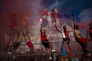 Supporters of the Santa Maria Novella Rossi Team light flares ahead of the match of the Calcio Storico Fiorentino in Piazza Santa Croce on 15 June 2019 in Florence, Italy.