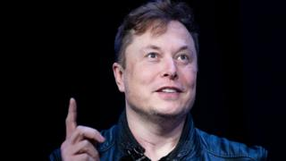 Elon Musk raises a finger while speaking in this file photo from March 2020