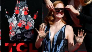 Actor Jessica Chastain is helped with her sunglasses after placing her hands in cement during a ceremony in the forecourt of the TCL Chinese theatre in Hollywood, Los Angeles, California