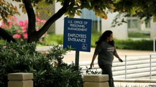 An employee of the US Office of Personnel Management departs the building in Washington - 5 June 2015