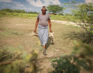 Mr Baisakhu carries animal bones in both hands
