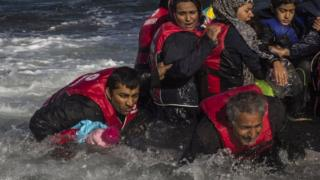 Migrants disembark from their boat on the Greek island of Lesbos after crossing the Aegean Sea from Turkey. File photo