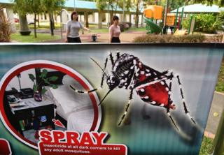 Residents walk to work past a public service announcement banner against the spread of Aedes mosquitoes, a carrier for the Zika virus, at a residential block at Aljunied Crescent neighbourhood in Singapore on August 29, 2016.