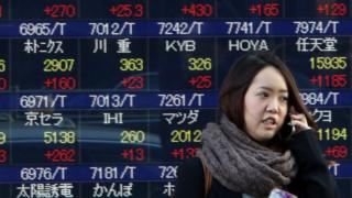 A woman passes before a share prices board in Tokyo on January 22, 2016.