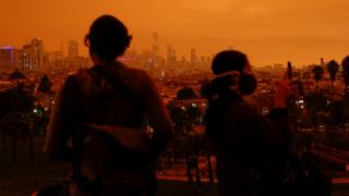 Visitors are seen in Dolores Park under an orange sky