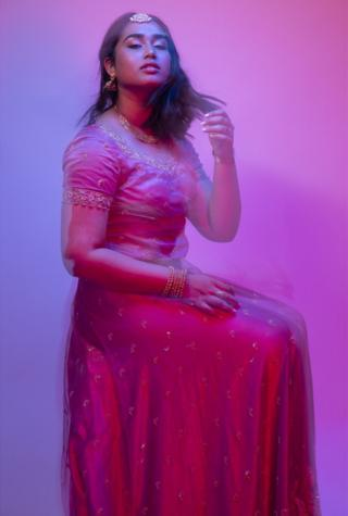 A portrait of a woman wearing a dress with a blurred effect implying movement