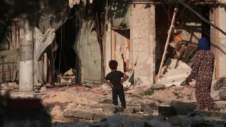Мальчик и денщина среди руин в Алеппо