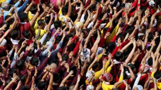 Filipino Roman Catholic devotees raise their hands in prayer during a procession to celebrate the feast day of the Black Nazarene on 9 January in Manila, Philippines