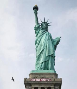 "A giant banner saying ""Refugees Welcome"" hangs on the pedestal of the Statue of Liberty, New York, 21 February 2017"
