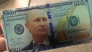 A Russian fridge magnet featuring Vladimir Putin on a $100 bill