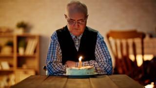 Elderly man celebrating birthday alone